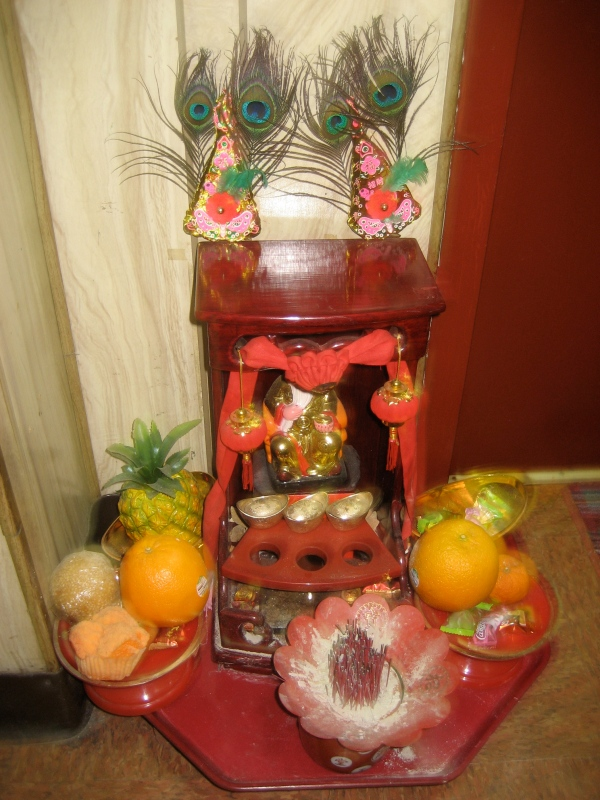 Altar outside someone;s apartment in my building... they are constantly adding fruit, incense and candies!!