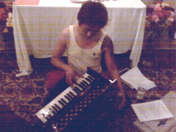kang sang practicing on the harmonium.